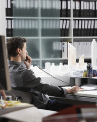 Businessman on telephone at desk in office