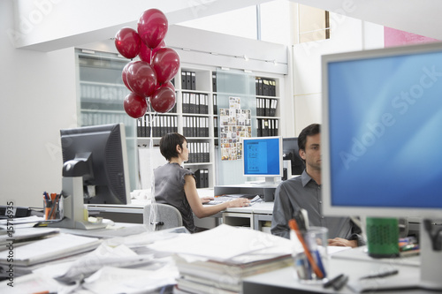 Businesswoman at desk with balloons tied to chair and coworker in foreground