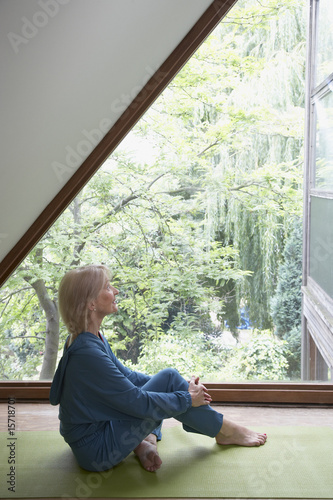 Woman sitting by a large window on a mat