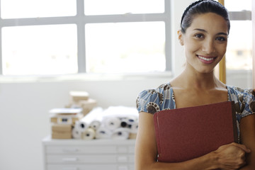 Businesswoman in office holding folder in arms