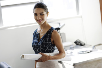 Businesswoman standing in office holding drafts under arm