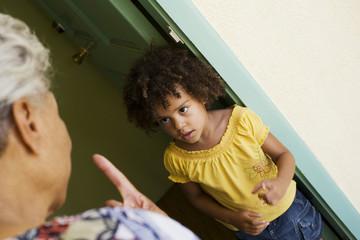 Woman scolding young girl in doorway