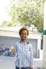 Boy standing in driveway with toy bubble gun