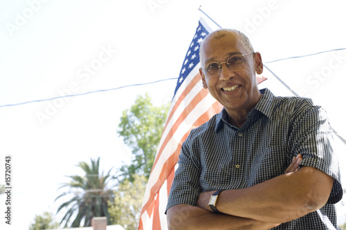 Man standing in front of American flag outdoors