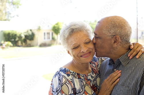 Man kissing woman on cheek outdoors