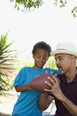 Man and young boy holding football