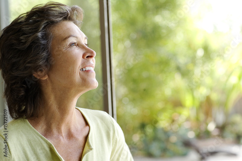 Woman looking up smiling in front of large windows