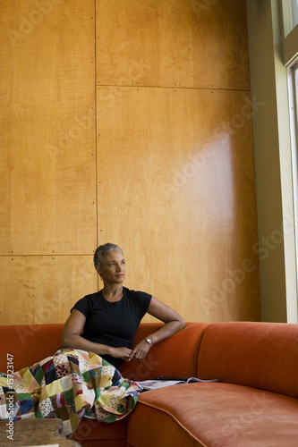 Woman sitting on sofa with a magazine in modern home