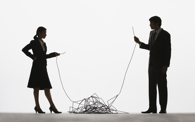 Businesswoman and businessman holding opposite ends of a long cable