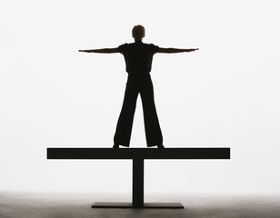 Woman standing on a plank with arms out