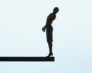 Woman standing on a plank looking over ledge