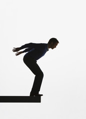 Man standing on a plank about to jump over ledge