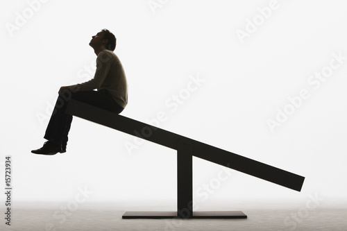 Man sitting on an unbalanced plank