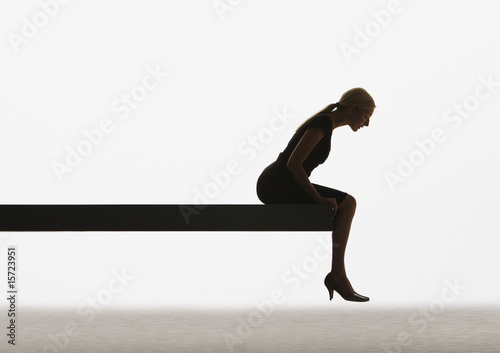 Woman sitting on a plank looking over ledge