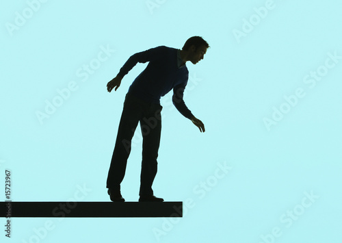 Man standing on a plank looking over ledge