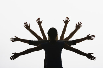 Four people with arms out so it looks like one person with eight arms