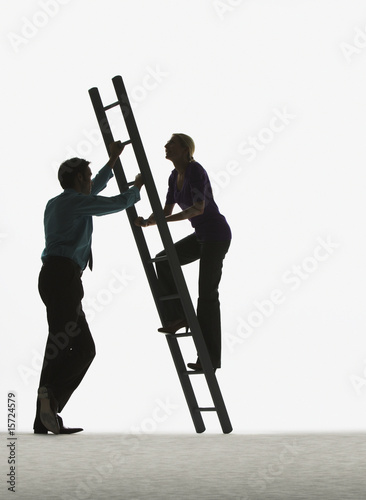 Man holding a ladder while a woman climbs it