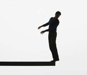 Man balancing on the edge of a plank