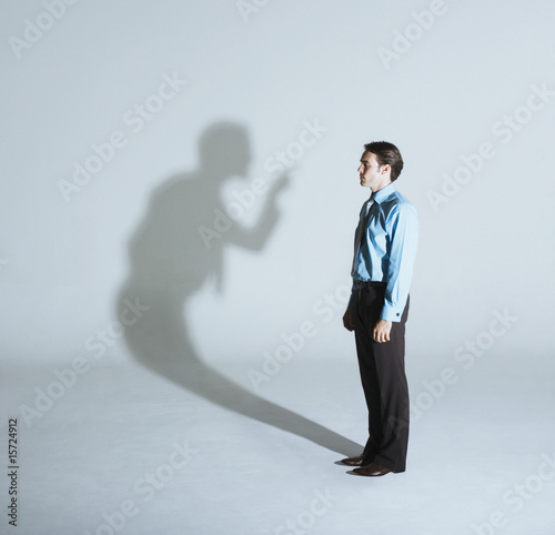 Man being scolded by his shadow