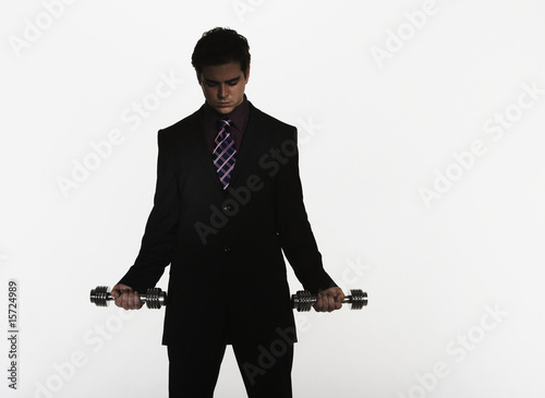 Businessman holding two small free weights