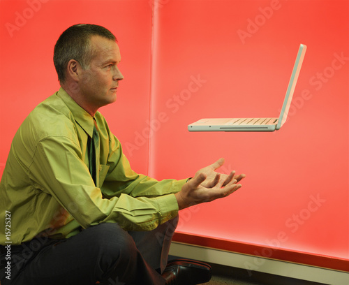 Man with floating laptop over him