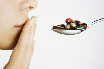 Woman with hand to mouth blocking spoonful of pills