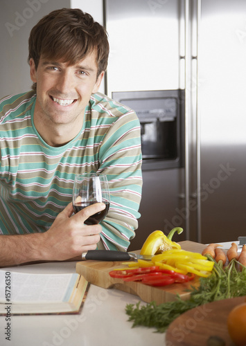 Man with a glass of wine and chopped peppers beside him