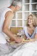 Man bringing woman breakfast in bed