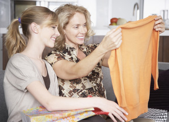 Woman looking at shirt with girl