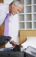 Man packing a suitcase in bedroom