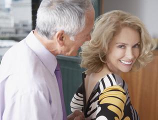Man helping woman with dress zipper