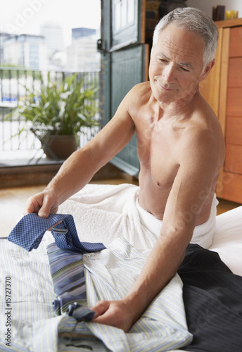 Man choosing tie on bed in modern home