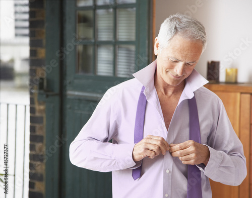 Man in bedroom getting dressed for work