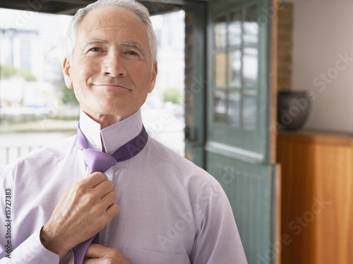 Man adjusting tie in bedroom