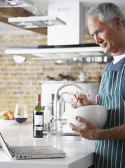 Man using whisk in bowl while looking at laptop