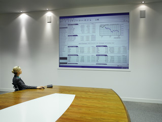 Businesswoman looking at large projection screen