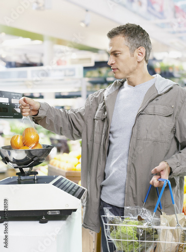 Man weighing fruit while in grocery store