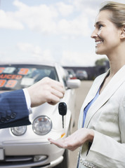 Man handing woman keys in car lot