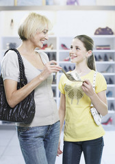 Woman and girl looking at shoes in store