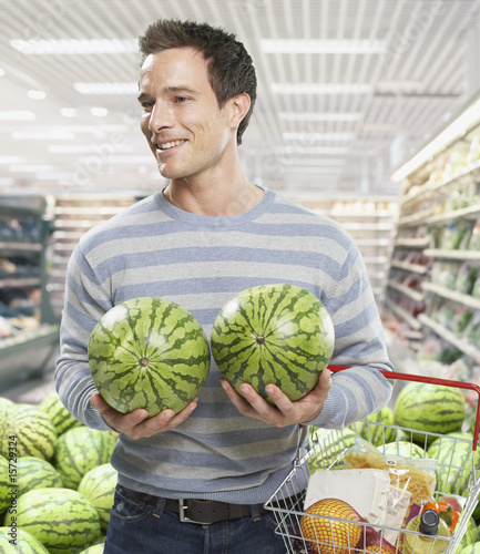 Man grocery shopping holding watermelons