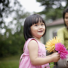 Girl holding flowers with woman in background