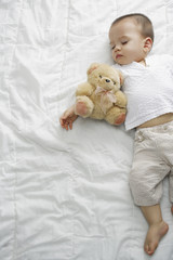Sleeping boy with teddy bear on bed