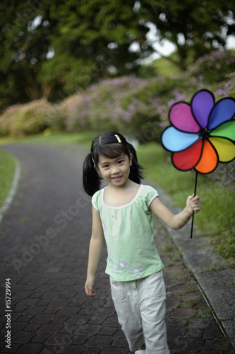 Girl holding windmill outdoors