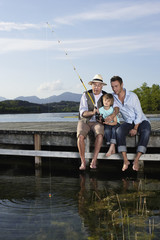 Two men fishing with young boy on dock