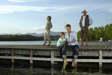 Man fishing with young boy on dock with couple in background