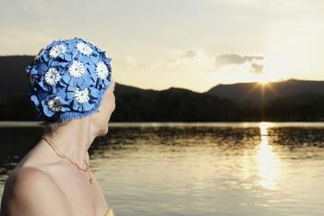 Woman wearing swim cap outdoors by lake