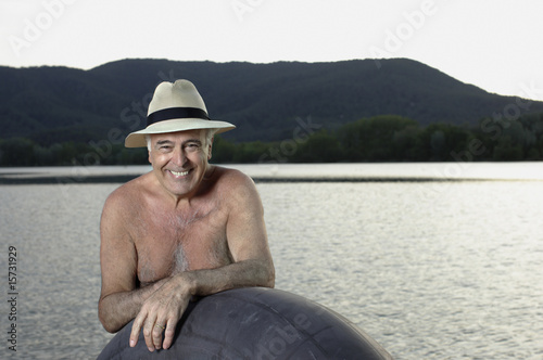 Man standing with inner tube by lake