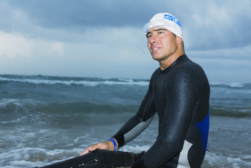 Man in wet suit sitting on shore of beach