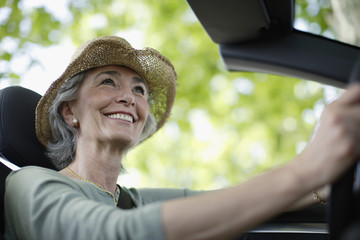 Woman driving convertible car wearing hat