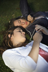 Two girls lying in grass with an MP3 Player